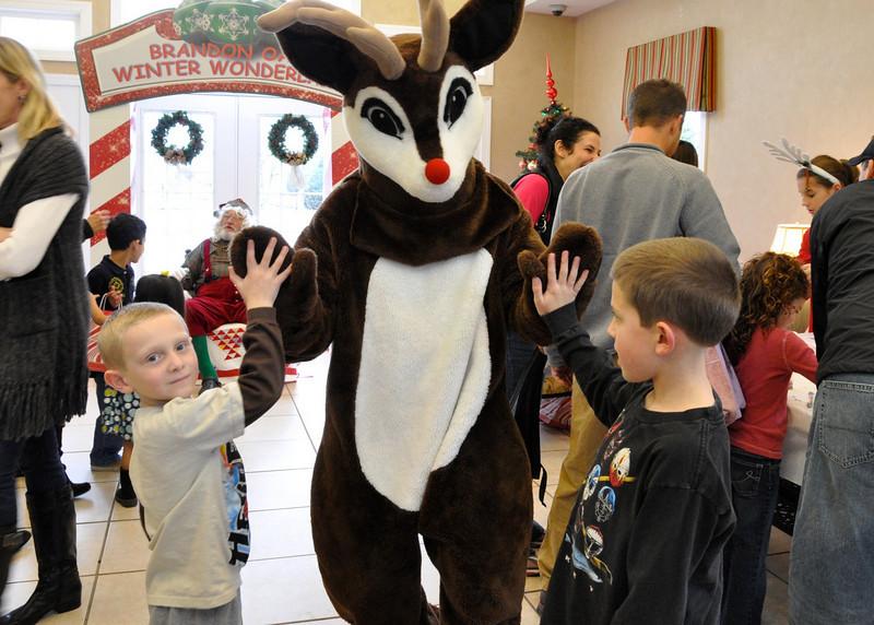 "Jonathan,6, Zachary,10, Renyhar giving ""high 5"" to Reindeer"