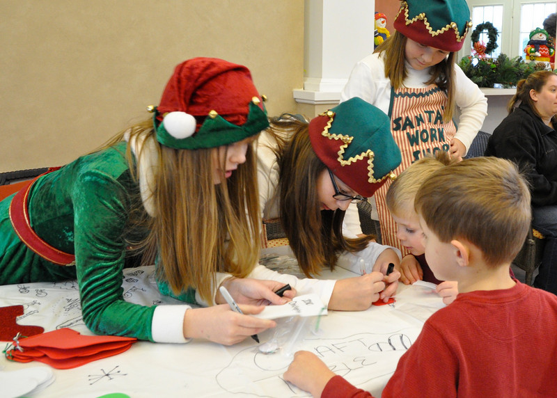 Santa's helpers lending a hand in the making of Christmas stockings.