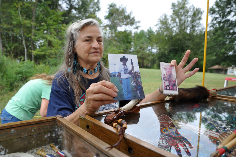 Margie Childers holds photos of Blue Eagle Crafts of Pembroke owner, Joyce Wilson, whose husband was awarded the congressional gold medal in 2007 as Tuskeegee airman Canadian Mohawk served in WWII called Black Fighters in Ramatelli, Italy hero that saved many US lives.