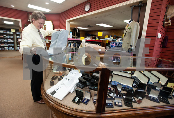 copyright 2012 Sarah A. Miller/Tyler Morning Telegraph  Penick & Chance owner John Chance looks for a flaw on a pair of slacks inside the men's clothing store located in the Olde English Village shopping center in Tyler. The store is closing their doors after 46 years.