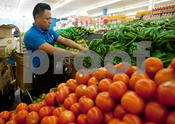 Supermercado Del Pueblo employee Jose Mateo stocks peppers in the produce aisle at the store Thursday April 30, 2015. The new grocery store is located at 2311 W. Erwin St. in Tyler.  (photo by Sarah A. Miller/Tyler Morning Telegraph)