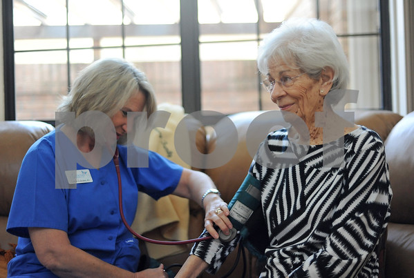 Linda Loicano, Genesis Home Care registered nurse, checks Dolores Strong's blood pressure in her home. (Victor Texcucao/Staff)