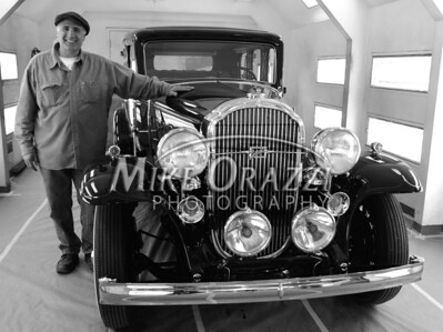 3/28/2009 Mike Orazzi | Staff Jesse Morton stands with a 1932 Buick Model 67 in his shop on Academy Street.