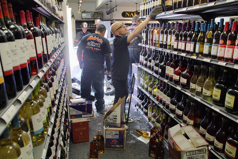 A blue Hyundai was driven through the window of Wyman's Liquors on Electric Ave. in Fitchburg Wednesday afternoon. An employee of Wyman's starts on the clean up while the car was still in the store. SENTINEL & ENTERPRISE/JOHN LOVE