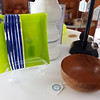 Green dish with blue stripe by Barbara Lester, and thin walled cherry bowl by woodworker John Santoro, at the Artisans Exchange in Central Square, Chelmsford.  (SUN/Julia Malakie)