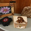"""Henna painting on wood by Vidhi Dalia of Westford, and slate coasters done with """"dot painting"""" by Hina Kaleem, at the Artisans Exchange in Central Square, Chelmsford.  (SUN/Julia Malakie)"""