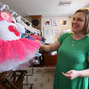 Eileen DeChaves of Chelmsford, one of the co-owners of the Artisans Exchange in Central Square, Chelmsford with tutus for babies from Shower the Baby Crafts, by Missy Casserly.  (SUN/Julia Malakie)