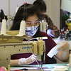 Assemble Lab sample maker Tien Tran of Everett sews section of filter material together at the company's space at Western Ave Studios, where they have switched from fashion orders to making masks for the COVID-19 pandemic. (SUN/Julia Malakie)