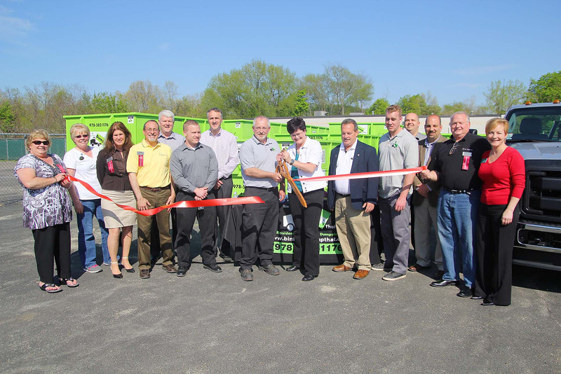 Owners of Bin There Dump That in Fitchburg held a ribbon cutting for their new company on Wednesday afternoon at their lot on Airport Road. Cutting ribbon, in center, is owners Mike and Julie Paradise with North Central MA Chamber of Commerce ambassadors and employees of the company. The new company is a mini disposal system that takes away any non hazardous items that municipal trash handlers will not. SENTINEL & ENTERPRISE/JOHN LOVE