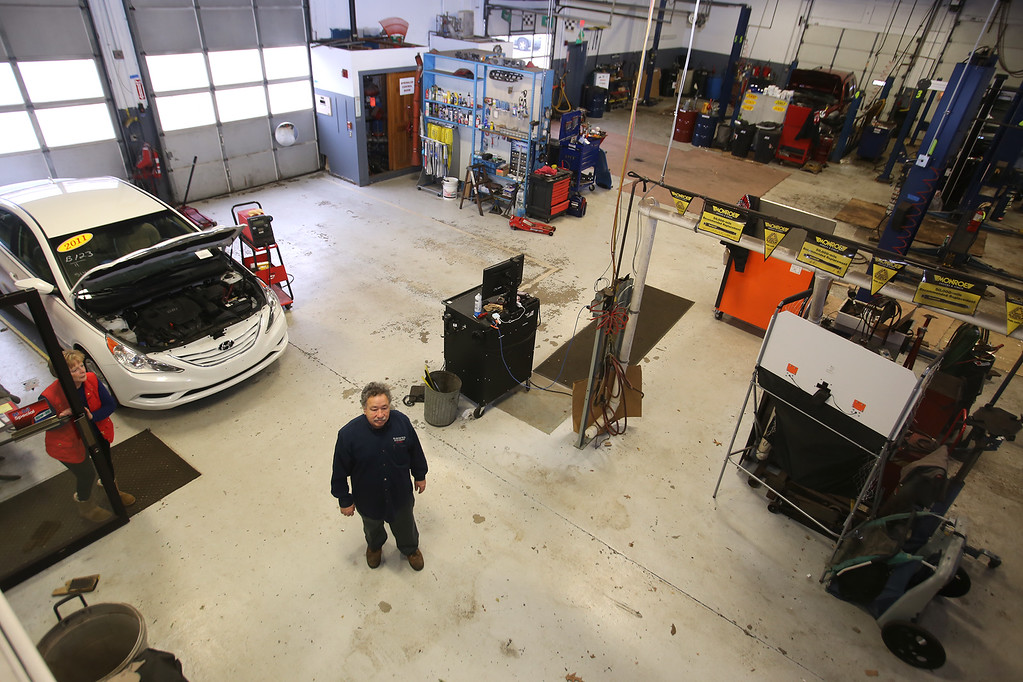 . Rich Blanchette, who is retiring this week after 41 years in business, having sold Blanchette\'s Automotive Service to Pep Boys. His wife Leanne Blanchette, who works part time in the office, is in the doorway at left.  (SUN/Julia Malakie)
