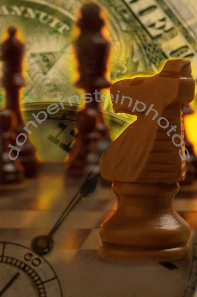 Chess pieces on board combined with imagery from U.S. currency and a watch is a metaphor/symbol for financial strategy and money management working with the concept of time.