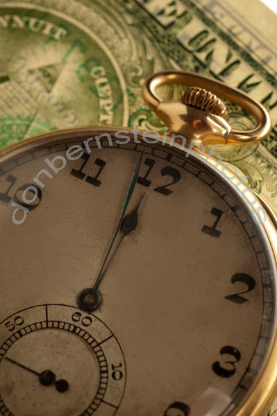 Antique time piece - pocket watch - combined with imagery from U.S. currency is a metaphor/symbol for time is money - the relationship between time and money.