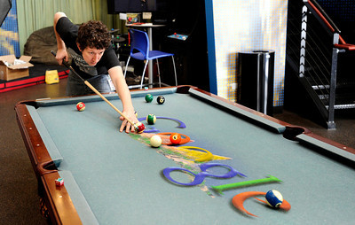 Google Building002.JPG Program Manager Jordan Van Wyk plays a game of pool in the Google break room on Tuesday, Feb. 7, at the Google building on Pearl Street in Boulder. For a video about the Google workplace environment go to www.dailycamera.com Jeremy Papasso/ Camera