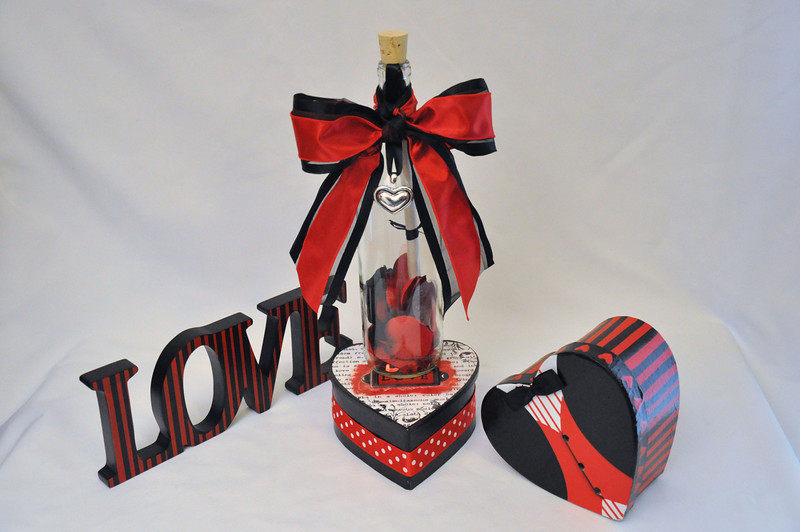 """Preserve and remember those moments when love feels like a bed of roses with this stunning Bordeaux bottle filled with red, black and white silk rose petals. This 12"""" charming message in a bottle is is sealed with your personalized message scroll and tied off with a beautiful red ribbon and elegant silver heart charm."""