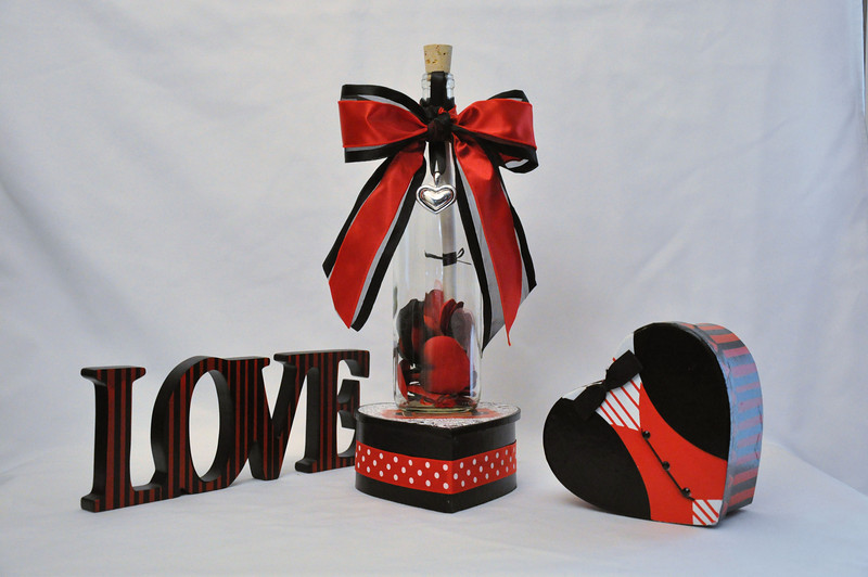 "Preserve and remember those moments when love feels like a bed of roses with this stunning Bordeaux bottle filled with red, black and white silk rose petals. This 12"" charming message in a bottle is is sealed with your personalized message scroll and tied off with a beautiful red ribbon and elegant silver heart charm.<br /> ."