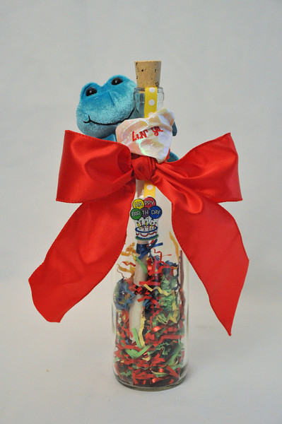 """Happy Birthday Bottle - Say Happy Birthday in a memorable way with this wonderful Happy Birthday bottle! This 12"""" Bordeaux bottle is filled with multi-colored and metallic happy birthday confetti for a birthday party in a bottle that will last through time. This fun and charming message in a bottle is sealed with your personalized happy birthday message scroll and topped off with a multi-colored happy birthday charm and memorable blue plush frog."""