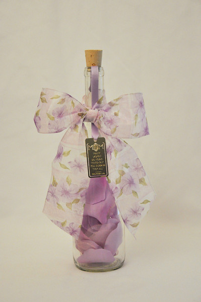 """Mother's Day Bottle - Give your mom or a mother close to your heart a permanent reminder of your love for them with this beautiful and charming message in a bottle. This 12"""" Bordeaux bottle is filled with pastel silk rose petals and lots of love before being sealed with your personalized message scroll and topped off with a pastel ribbon and bow and beautiful brass plated Mother's Day bookmark."""