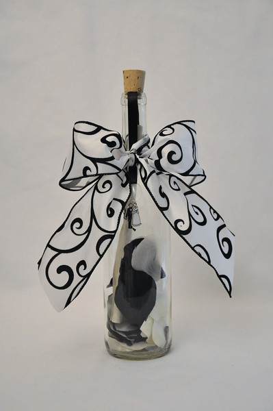 """Wedding Bottle - Give a gift a bride and groom close to your heart are sure to remember and appreciate. This beautifully crafted 12"""" Bordeaux bottle is filled with black and white silk rose petals and your personalized message scroll, sealed with a silver heart bottle stopper as a representation of love. This charming message in a bottle is finished off with black and white ribbon, a beautifully crafted bow, and a gorgeous silver wedding charm."""