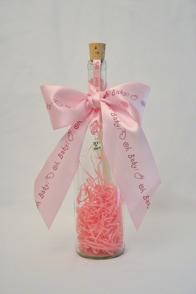 """It's A Girl Bottle - Give a unique and precious gift a special family and mother-to-be in your life is sure to appreciate. This fun It's a Girl bottle includes your personalized message scroll enveloped in celebratory pink confetti inside a beautiful 12"""" Bordeaux bottle. This charming message in a bottle is finished off with an adorable pink pacifier and pink and white """"It's a Girl Ribbon"""" to mark a joyous occasion."""