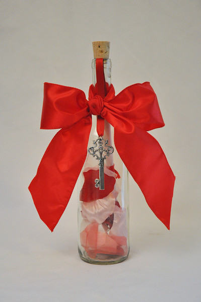 "Key To My Heart Bottle - Red roses are the symbol of not just love, but also courage, respect, beauty and passion. Give someone special in your life a permanent key to your heart and reminder of your feelings with this beautifully crafted Bordeaux bottle filled with red silk rose petals. This 12"" charming message in a bottle is sealed with your personalized elegant message scroll and tied off with a beautiful red ribbon and elegant silver key charm."