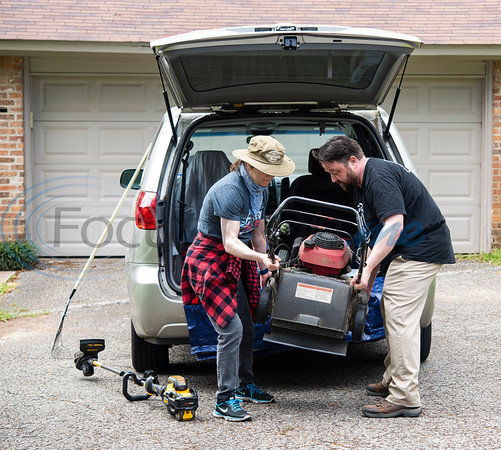 """Liz Cace helps her fiancé Clay Riggs unload his lawn mowing equipment at a house in Tyler, Texas on Wednesday, April 1, 2020. Riggs, owner of Clay's Cuts, and a barber for 16 years, switched to a lawn mowing service as businesses were being closed due to the coronavirus. Gov. Greg Abbott ordered all non-essential business in Texas to close, including barber shops and hair salons. On March 30, the Clay's Cuts Facebook page announced: """"Clay's Cuts lawn service is go! Covid-19 has closed the shop, but I can clean your yard without getting too close to you. If you need some yard work done, please call 9038059566. Raking, mowing, weed-whacking and more! Liz and I are happy to help! Thanks for your support!"""""""
