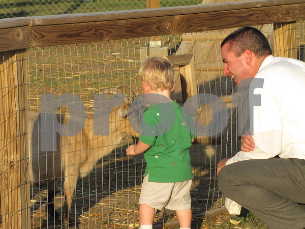 Noah Flaherty shows his dad how to feed the goats at the 'Back 40 Playground' .