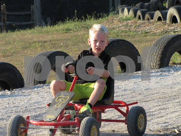 Micah Flaherty racing a go-cart at the 'Back 40 Playground' at the Community Orchard.