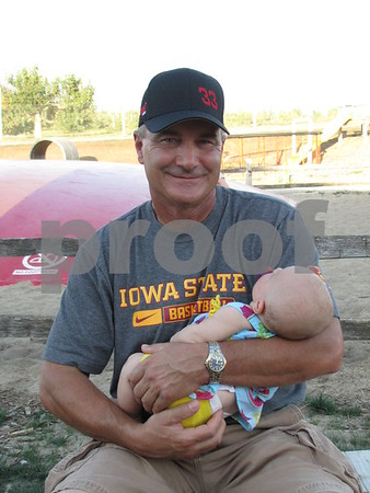 Kim Martin found a shady spot for he and his granddaughter, Kiley Norine, while attending the Northwest Bank celebration at the Community Orchard.