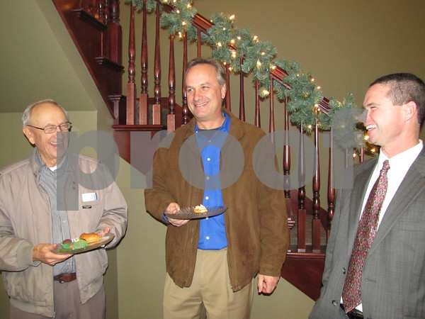 Leroy Schwendemann and his son, Gary Schwendemann, share a laugh with Sid Bodholdt at Northwest Bank's holiday open house.