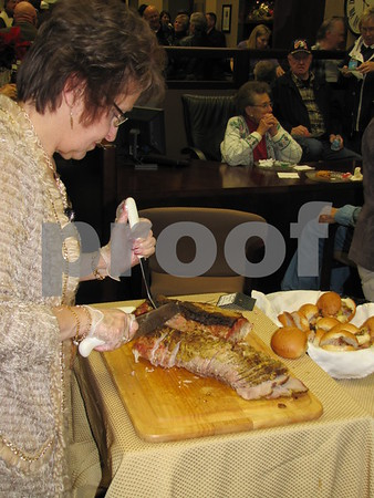 Debra Lacina of Tea Thyme serves pork loin at the buffet at Northwest Bank's holiday open house.