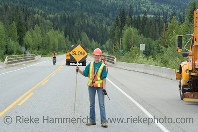 Female road worker holding Stop and Slow Sign - Highway 18 in British Columbia, Canada