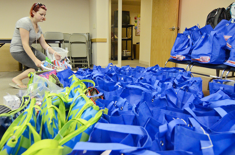 Cyleste Johnson, 19, part of Help for Our Communities, a Fitchburg-based charity group, places supply bags for children in foster care in a pile at the DCF office in Leominster on Tuesday evening. SENTINEL & ENTERPRISE / Ashley Green