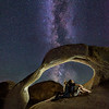 """<span class=""""AaronsSubTitle"""">Milky Way Through Mobius Arch Alabama Hills Recreation Park, Lone Pine, California</span>  Superstar photographer Ben Von Wong joined SmugMug on our epic company retreat this year in Park City Utah and I enjoyed getting to know him and his girlfriend Anna over the 7 day trip. When they asked me to cancel my flight home and spend 4 days driving to San Francisco with them and Nick, I knew I couldn't refuse!  I shouldn't have been surprised to learn that Ben, whose photographs always include people, didn't have the patience to wait for Nick and I to do our landscape photographer thing. As long as the hike or the scene would be epic we might capture his interest long enough not to make us pack up and head somewhere else. We hiked The Narrows. We walked the Vegas strip. We explored eroded landscapes and salt flats in Death Valley. And on the last night we showed him the Milky Way for the first time with his naked eye. Ben and Anna have been creating a """"selfie-series"""" of photographs, taking fun and unique portraits of themselves in unique places. Mobius Arch was going to be another stop in this series.   We made our way to the Alabama Hills in Lone Pine, California and arrived at Mobius Arch just after sunset. We made a quick stop to use the """"Sky Guide"""" app to figure out when the Milky Way would align properly and went off to grab a pizza dinner. When we got back to the arch, Ben knew immediately where he'd be setting his camera down for his epic Milky Way selfie! I on the other hand, struggled for almost an hour to find a composition that I liked (for an epic landscape). That's when I decided """"you know what, let's get in on this portrait photo!"""" I found a different spot to place my camera and while Ben composed his as a landscape photo, I placed my camera as portrait orientation.  To capture this photo Ben and I would set my camera on a 10-second timer. At the 8 second mark, Ben would use an app on his Android phone to trigger a 2-second time"""