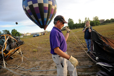 Pilot Michael Gianetti of Life Cycle Balloon Adventures sets up his balloon as Barbara Patrick assists before a passenger flight  in the Gunbarrel area of Boulder on Thursday morning.  FOR MORE PHOTOS AND A VIDEO OF THE LIFTOFF GO TO WWW.DAILYCAMERA.COM  Photo by Paul Aiken / The Camera / 8/ 18/ 2011