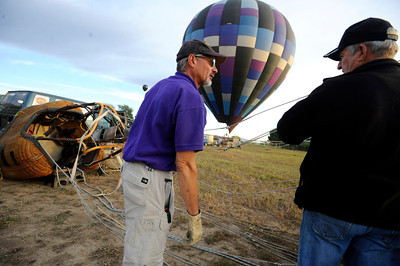 Pilot Michael Gianetti, left,  of Life Cycle Balloon Adventures gives instructions to passenger Gene Schiferl who volunteered to help set up the balloon before a  flight  in the Gunbarrel area of Boulder on Thursday morning.  FOR MORE PHOTOS AND A VIDEO OF THE LIFTOFF GO TO WWW.DAILYCAMERA.COM  Photo by Paul Aiken / The Camera / 8/ 18/ 2011