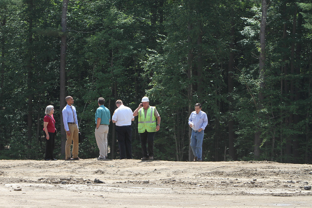 . Groundbreaking ceremony for the Four Corners MassWorks Infrastructure Project, at the intersection of Rt 119 and Rt 225 in Groton. Attendees look over the rim of the excavation for the sewer connection infrastructure. (SUN/Julia Malakie)