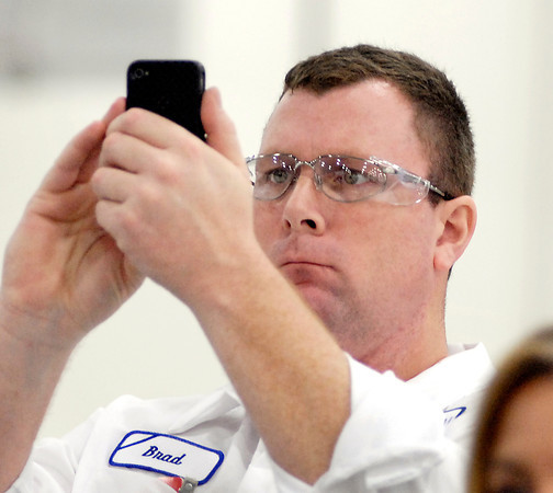 A GTI employee takes photos on his phone of the ribbon cutting ceremony.