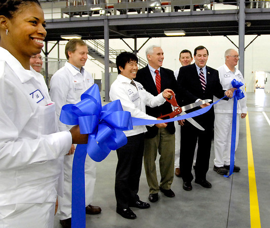 Sho Kurita, holding scissors, GTI president & CEO, is all smiles along with other dignitaries as he prepares to cut the ribbon to officially open GTI's new parts manufacturing plant in Anderson.