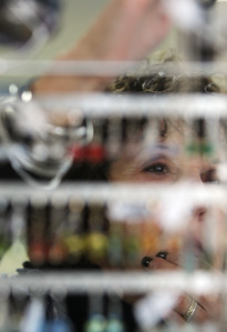 A friend of Facets etc. owner Tracy Smith fills in at the shop on Hollis Street in Groton, pricing and hanging up earrings at the store that sells jewelry and artisan gifts. (SUN/Julia Malakie)
