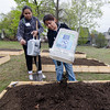 Jacquelin and Alejandras Contreras fill their plot with dirt during the grand opening of Growing Places new teaching garden at St. Joseph's Church in Fitchburg on Saturday afternoon. SENTINEL & ENTERPRISE / Ashley Green