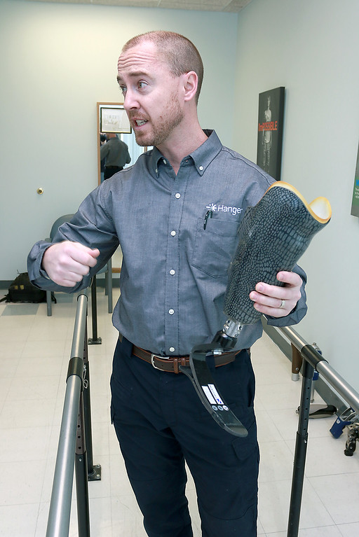 . Brian Heckathorn, CPO (certified prosthetist, orthotist) and area clinic manager with Hanger Clinic talks about their prosthetics, while holding one, on Thursday at their Leominster office. SENTINEL & ENTERPRISE/JOHN LOVE