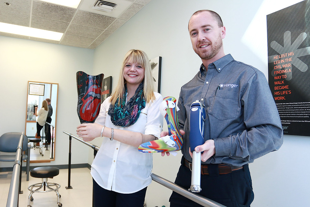 . Brian Heckathorn, CPO (certified prosthetist, orthotist) and area clinic manager with Hanger Clinic with Maggie Baumer, JD business development manager as she show off a few of their prosthetics on Thursday at their Leominster office. SENTINEL & ENTERPRISE/JOHN LOVE