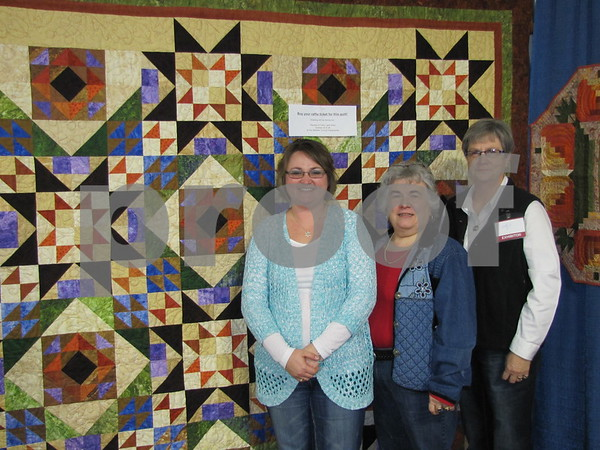 Jennie Ort, Nancy Griffel, and Betty Scheidegger of the Fort Dodge Area Quilters stand in front of the beautiful quilt they were raffling off.