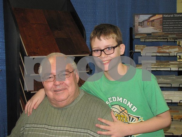Larry Leiting with his grandson Sean Flattery in the booth of Flooring America Carpet World.