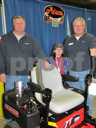 Denny Staley of Casady Bros. Implement of Webster City with Karli Robinson, and John Hessenius the Ariens Representative stand behind one of the riders they had on display.