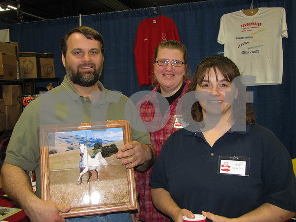 Travis, Kathryn, and Tricia Bell show off one of the printed tiles they produce at Bell Family Creations in Rockwell City.