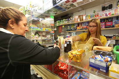 Infante Grocery co-owner Dayris Cruz, right, serves customer Ana Rios of Lowell. (SUN/Julia Malakie)