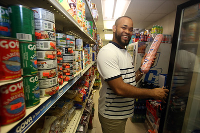 Garibaldy Cruz, co-owner with his wife of Infante Grocery on Broadway in Lowell, which carries many imported vegetables and brands. He's holding Induveca salami, a Dominican brand. (SUN/Julia Malakie)