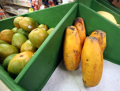 Mangos, left, and papayas, at Infante Grocery on Broadway in Lowell, which carries many imported vegetables and brands. (SUN/Julia Malakie)