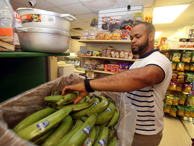 Garibaldy Cruz, co-owner with his wife of Infante Grocery on Broadway in Lowell, which carries many imported vegetables and brands, bags plantains in bags of three or four. Plantains are a staple that brings in customers. (SUN/Julia Malakie)